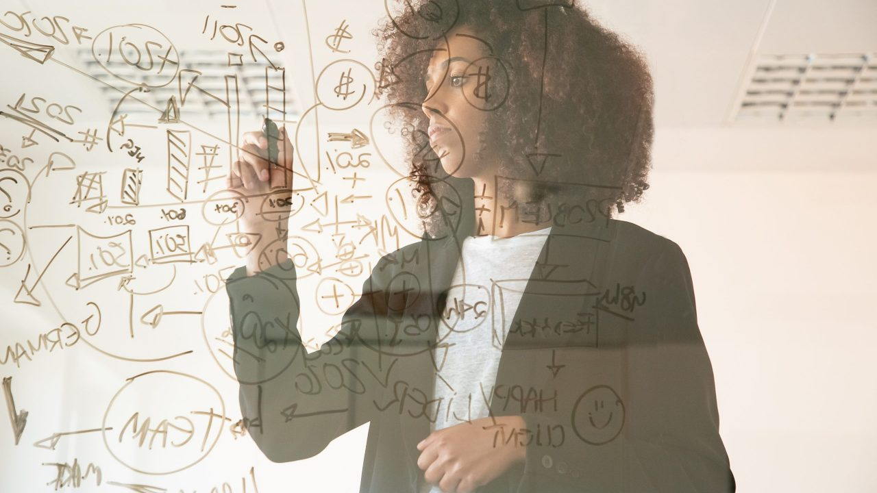 Focused young businesswomen writing on virtual board. Concentrated young African American female manager holding marker and making noted on chart. Strategy, business and management concept